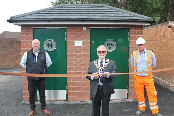 chairman cutting ribbon in front of toilets with a man either side of him