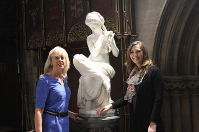 Two tourist information assistants next to statue of the Reading Girl