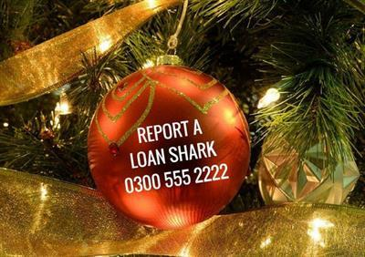 bauble on a Christmas tree with loan shark text including phone number