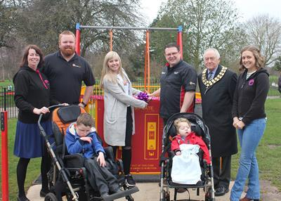 Stephanie Hufton cutting the ribbon in front of the accessibility swing, accompanied by the chairman, other fundraisers and two boys in wheelchairs