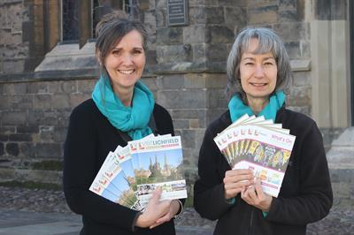 Two women from Visit Lichfield holding the guide and What's on brochures in front of St Mary's