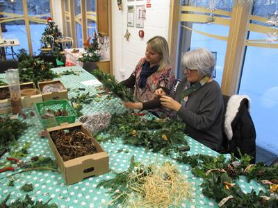 two women making a wreath