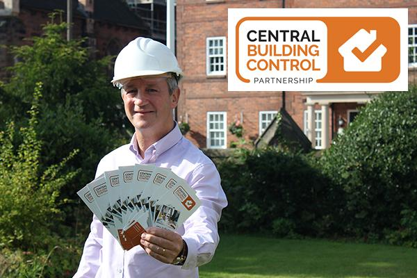 man in hard hat holding leaflets to cameral