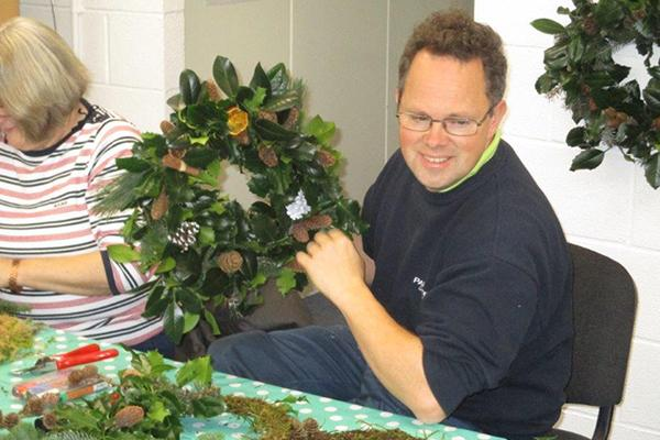 Man at workshop holding Christmas wreath.