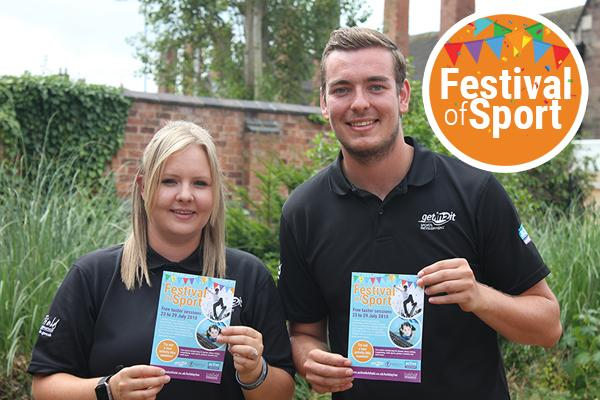two sports development officers holding festival of sport programme
