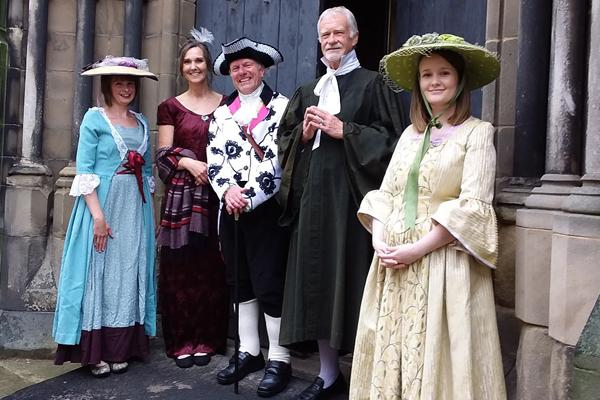 people in historical dress in front of historical buildings.