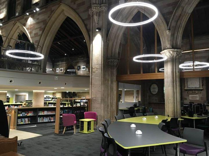 library interior with bookshelves, a reception desk and hanging lights that look like halos