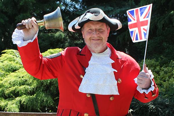 Ken Knowles in town crier costume, holding bell and union flag