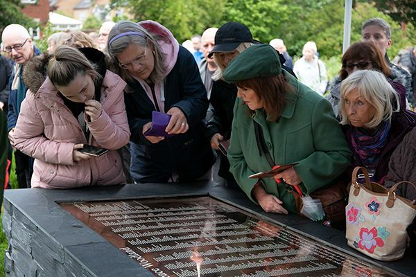 people looking at names on a plaque