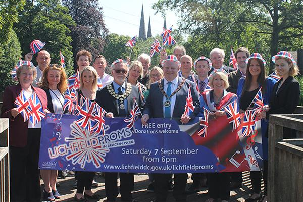 sponsors in a group holding a proms banner and flags