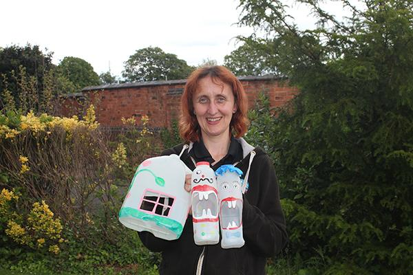 Woman holding decorated milk bottles