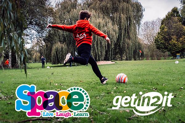 boy playing foot golf with space and getin2it logo