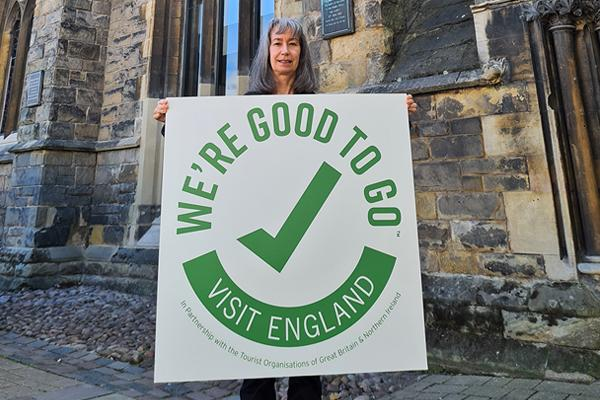 Woman holding We're Good To Go sign in front of historic building