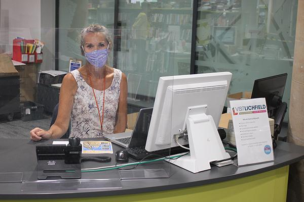 woman wearing a face mask behind a desk