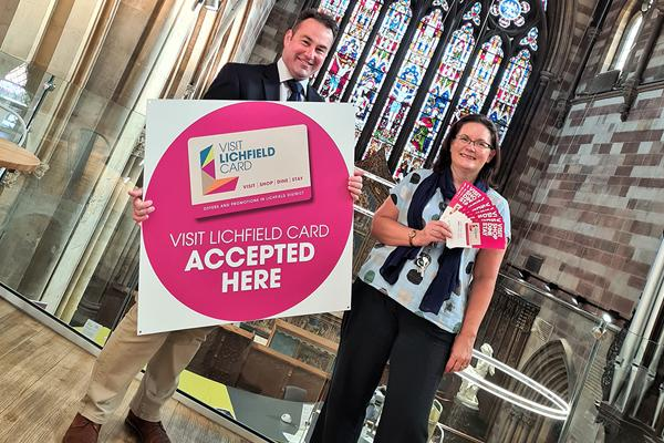Iain Eadie holding a big sign that says Visit Lichfield card accepted here, stood next to Louise Flemming holding leaflets