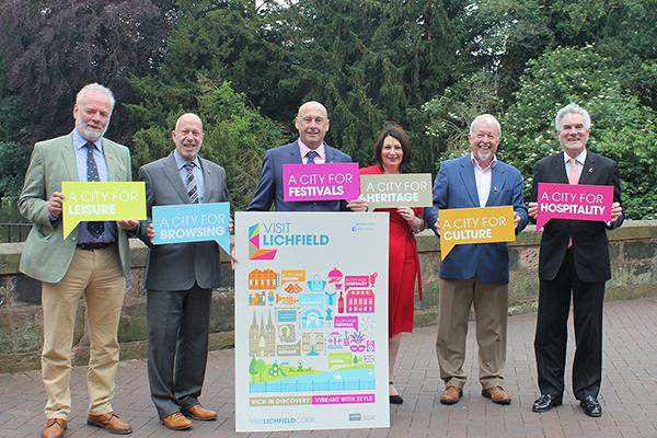 six people stood in front of a Visit Lichfield advert holding bright speech bubbles