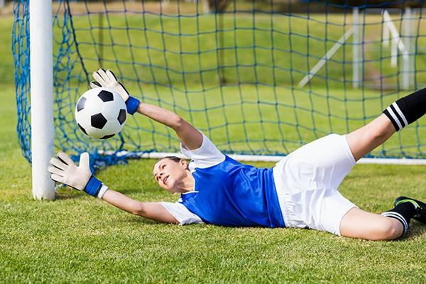 Female goal keeper diving to save a football