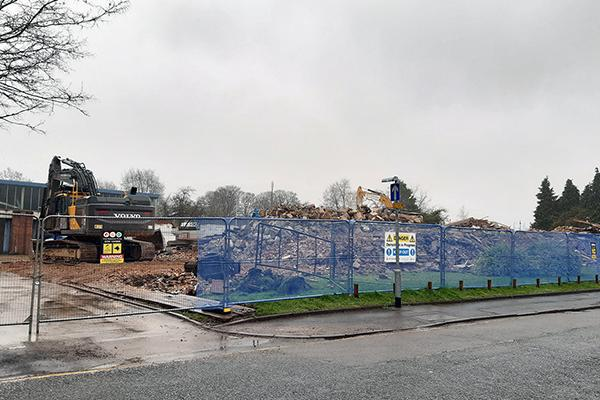 Image of the demolished police station showing lots of rubble and a demo truck