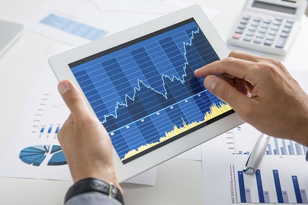 male hands holding tablet which has a graph on it showing growth