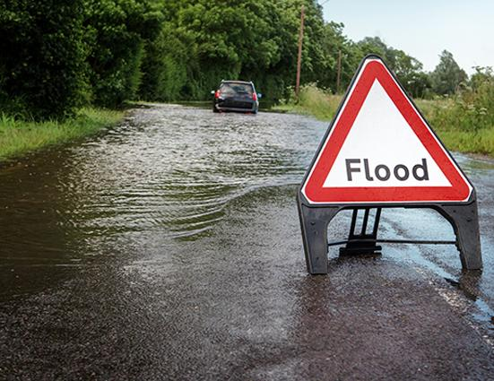 image of flooded road and roadsign saying flood
