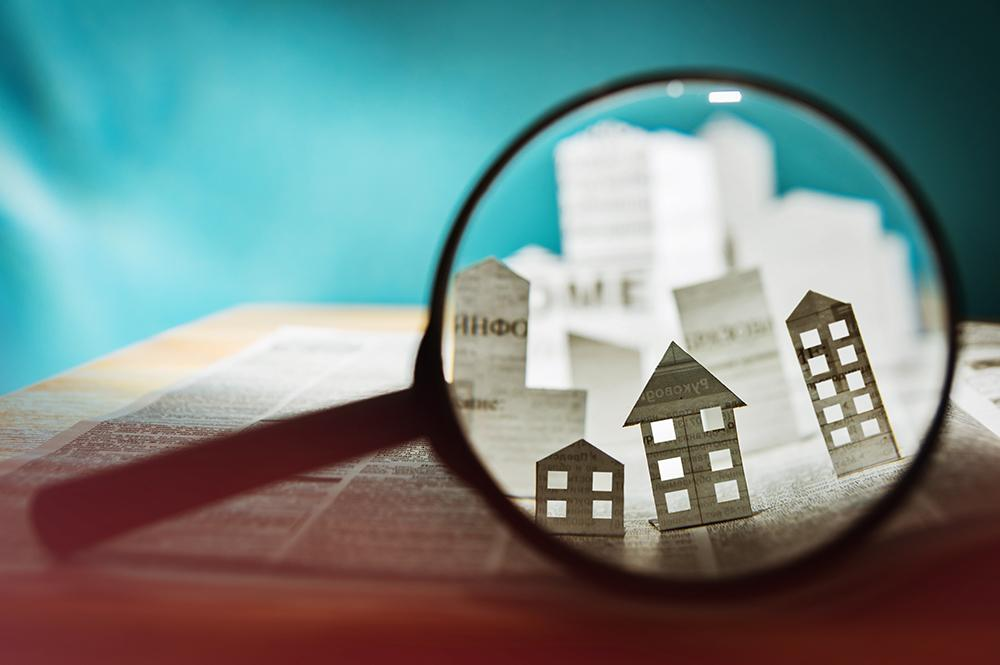 houses made of paper under a magnifying glass