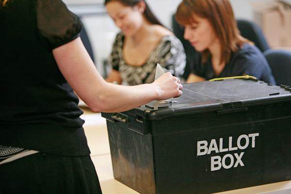 woman placing vote in ballot box